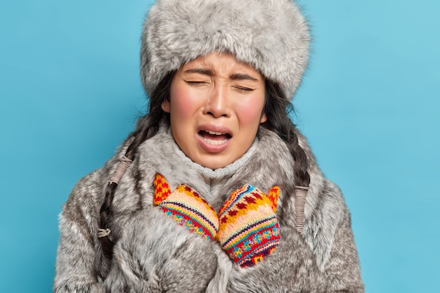 Close-up shot van ontevreden jonge aziatische inuit vrouw draagt gebreide wanten en winter outfit voelt koud aan tijdens de ijzige winter geïsoleerd over blauwe muur