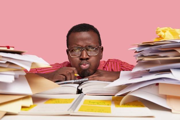 Close-up shot van ontevreden student pruilt lippen, blaast wangen, mannetjes schetst in spiraal dagboek, leunt hoofd op bureau, omringd met stapels papieren en literatuur