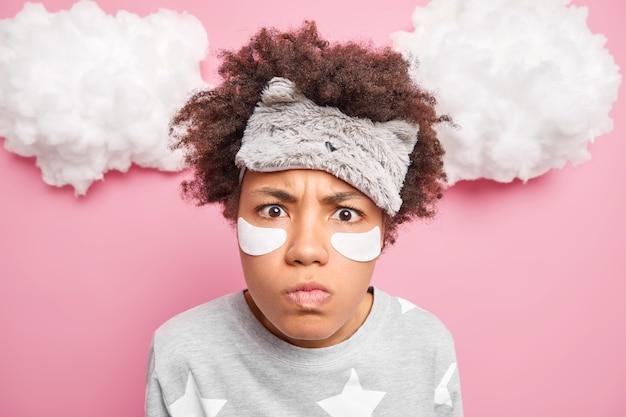 Close-up shot van ontevreden vrouw met krullend haar kijkt geschokt naar camera draagt blinddoek en pyjama geïsoleerd over roze muur heeft slecht humeur na ontwaken
