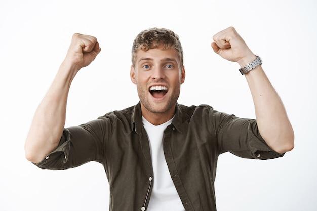 Close-up shot van opgewonden en opgetogen gelukkige europese man die vuisten opheft in triomf en viering ja vreugdevol schreeuwend als hoopvol en opgewonden aan de voorkant poserend tegen een grijze muur