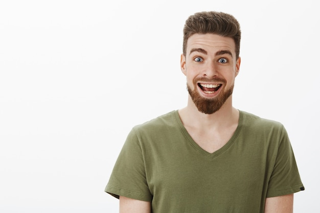 Close-up shot van opgewonden en verbaasd verbaasd gelukkig bebaarde man die wenkbrauwen optrekt en de ogen wijd openzet breed glimlachend terwijl hij een onverwacht geweldig aanbod van het leven ontvangt over een witte muur