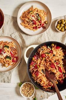Close-up shot van pasta met groenten en ingrediënten op een witte tafel
