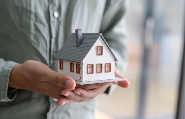Close-up shot van persoon model huis in de hand te houden