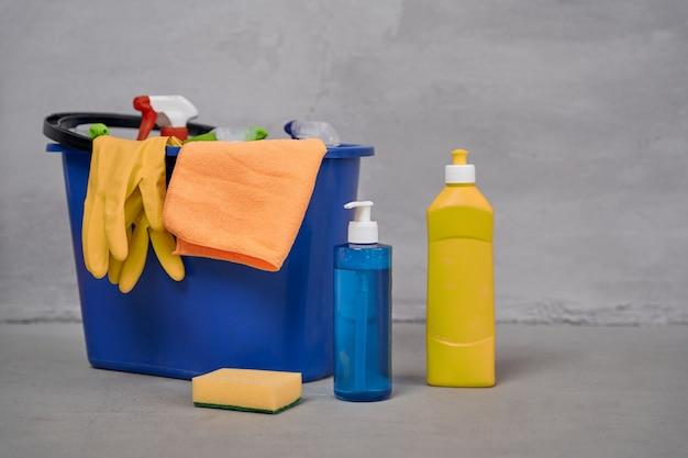 Close-up shot van plastic emmer met schoonmaakproducten en flessen met wasmiddelen die op de vloer staan tegen de grijze muur. huishoudelijk werk, schoonmaak, huishoudconcept. desinfectie