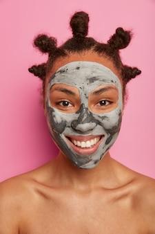 Close-up shot van positieve vrouw geniet van gezichtsbehandeling, past kleimasker toe, glimlacht breed, heeft witte tanden, staat naakt alleen, voelt zich ontspannen, geïsoleerd over roze muur. verfrissend, spa, lichaamsverzorging