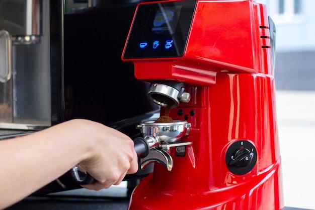 Close-up shot van professionele barman espresso koffie bereiden in exclusieve café-bar of cafetaria. hij gebruikt koffiemolen of koffiemolen.