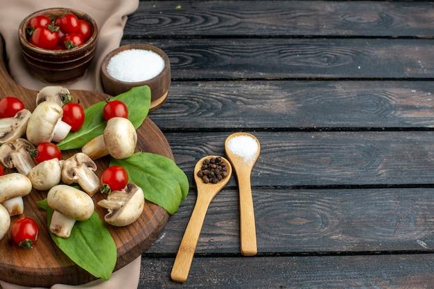 Close-up shot van rauwe verse champignons en tomaten kruiden op houten plank handdoek op zwarte achtergrond