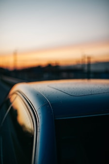 Close-up shot van regendruppels op het dak van een auto met de avondrood weerspiegeld in de ramen