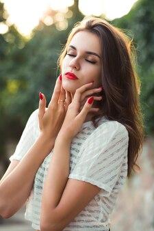 Close-up shot van romantisch brunette model met rode lippen poseren met gesloten ogen