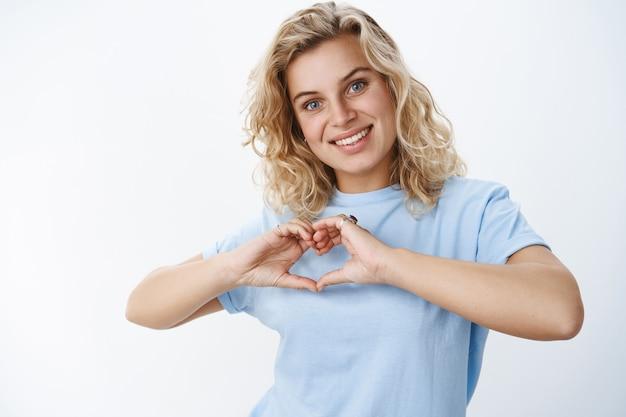 Close-up shot van romantische en schattige vriendin met blauwe ogen en kort blond kapsel glimlachend warm en lief, met een hartteken over de borst die liefde en sympathie uitdrukt, een hartverwarmend gebaar makend
