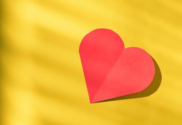 Close - up shot van rood papier hart op gele achtergrond en schaduw voor valentijn.
