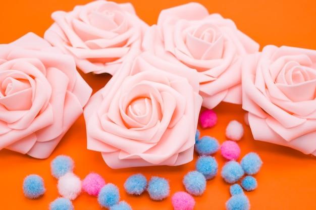Close-up shot van roze rozen en kleurrijke pompons geïsoleerd op een oranje achtergrond