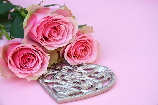 Close-up shot van roze rozen met een metalen hartvorm op een roze oppervlak