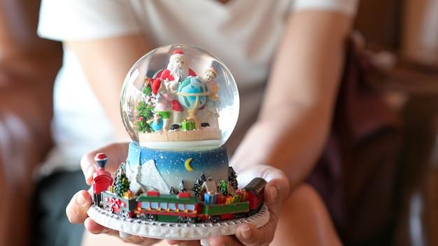 Close-up shot van santa pop in een kristallen bol in de hand van een vrouw voor kerstmis.