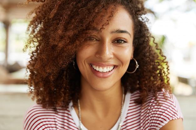 Close-up shot van schattige afro-amerikaanse vrouw heeft een brede glimlach, draagt een gestreepte t-shirt, in goed humeur, rust in cafetaria met beste vrienden. glimlachend donkere huid jonge vrouw vormt binnen