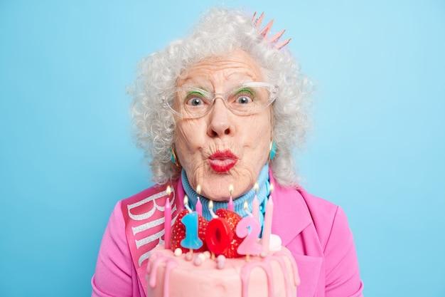 Close-up shot van senior vrouw met grijs krullend haar houdt de lippen gevouwen om kaarsen op de taart te blazen viert verjaardag goed gekleed te zijn heeft lichte make-up geniet van speciale gelegenheid krijgt gefeliciteerd