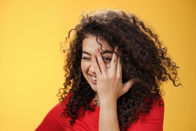 Close-up shot van sensuele en speelse aantrekkelijke vriendin met krullend haar die gezicht bedekken met palm en gluren door de vingers met een gelukkige tedere glimlach anticiperend op verrassing over gele achtergrond.