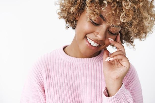Close-up shot van sensuele en tedere afro-amerikaanse vriendin met blond kapsel die zacht en lieflijk staarde glimlachend lieflijk en verlegen neerkijkend alsof ze het aanraken van het gezicht over de witte muur verleidt