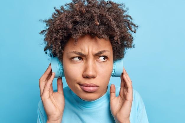 Close-up shot van serieuze vrouwelijke student met krullend haar luistert audioboek kijkt aandachtig ergens houdt handen op stereo hoofdtelefoon geïsoleerd over blauwe muur heeft ontevredenheid expressie