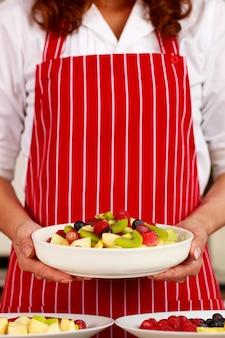 Close-up shot van smakelijke lekkere heerlijke zoete gemengde fruitsalade voorgerecht appel kiwi bosbes druif in witte kom op uitvoerende vrouwelijke chef-kok handen die staan streep rode schort achter op achtergrond draagt.