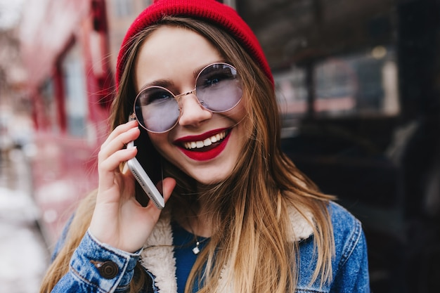 Close-up shot van spectaculaire vrouw in rode hoed iemand bellen in de lentedag.