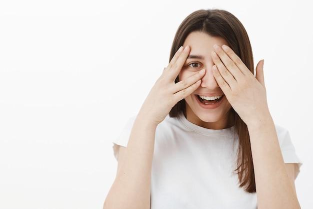 Close-up shot van speelse schattige en uitgaande jonge brunette in wit t-shirt met plezier, lachen en glimlachen als kiekeboe spelen, ogen sluiten met handpalmen gluren vreugdevol door vingers