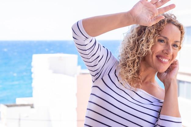 Close-up shot van stijlvolle krullende vrouw die lacht tegen de achtergrond van de blauwe zee. mooi vrouwelijk model met kopieerruimte