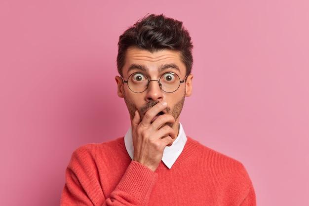 Close-up shot van stomverbaasde donkerbruine volwassen man bedekt mond en staart afgeluisterde ogen door bril hoort schokkend nieuws
