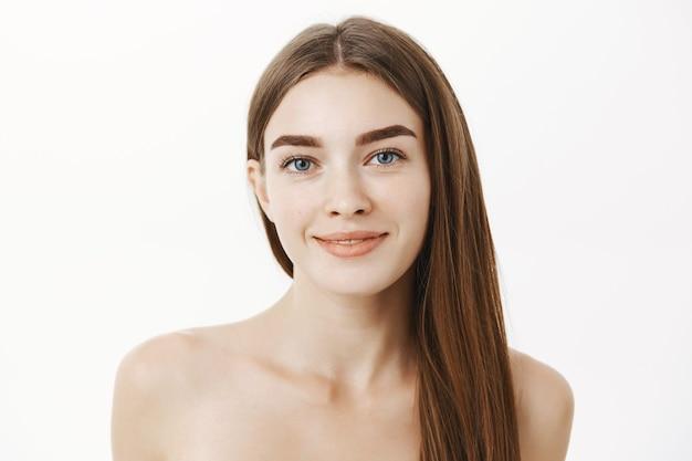 Close-up shot van tedere en vrouwelijke schattige jonge vrouw met lang bruin haar die naakt over een grijze muur staat en glimlacht zonder puistjes, tevreden is met perfecte pure huidconditie over grijze muur