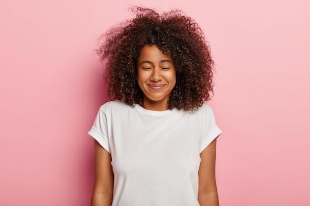 Close-up shot van tevreden mooie tiener met borstelig krullend haar, ogen dicht, aangename glimlach, wacht op verrassing met groot geluk, geniet van geweldige tijd in het weekend, draagt een wit t-shirt