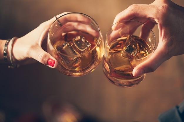 Close-up shot van twee mensen rammelende glazen met alcohol op een toast