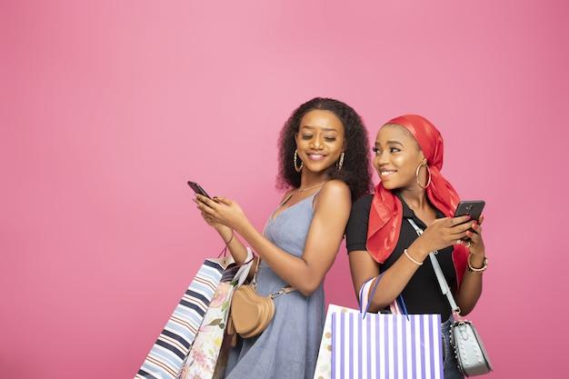 Close-up shot van twee mooie afro-amerikaanse meisjes die hun telefoons gebruiken terwijl ze boodschappentassen vasthouden