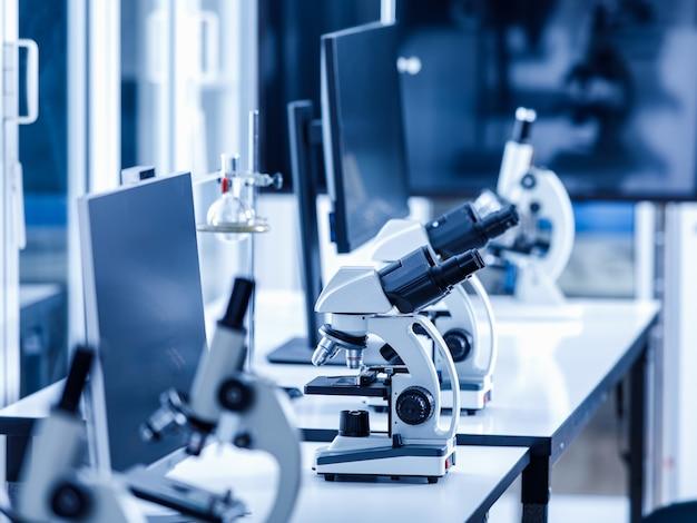 Close-up shot van twee ogen zoeker wetenschappelijke microscoop in rij van één oog microscopen lijn in wazige voorgrond op laboratorium werktafel gebruikt voor het monitoren van coronavirus covid 19 virusmonsters.