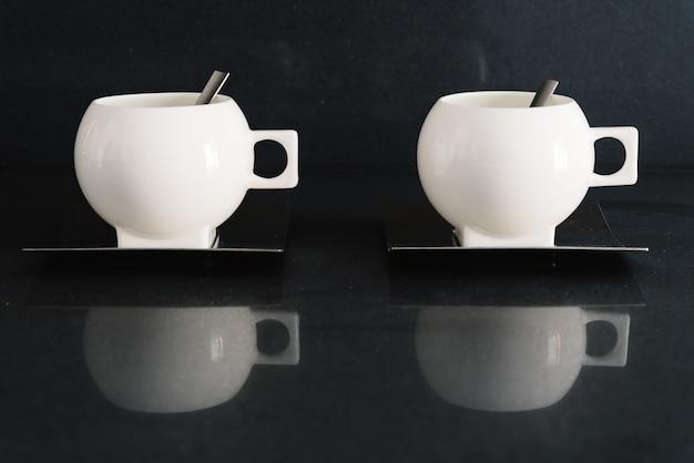 Close-up shot van twee witte kopjes met lepels binnen in een donkere betegelde keuken