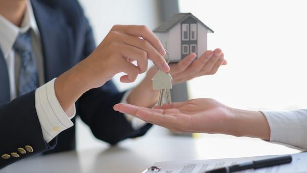 Close-up shot van vastgoedmakelaar levert bouwsleutels aan klanten.