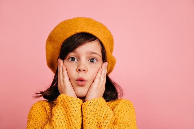 Close-up shot van verbaasd meisje grappige gezichten maken. europees kind in gele baret.