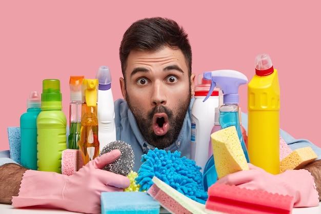 Close-up shot van verbaasde knappe jongeman met dikke stoppels, houdt de mond open van verbazing, gebruikt detergenten voor het schoonmaken van de kamer