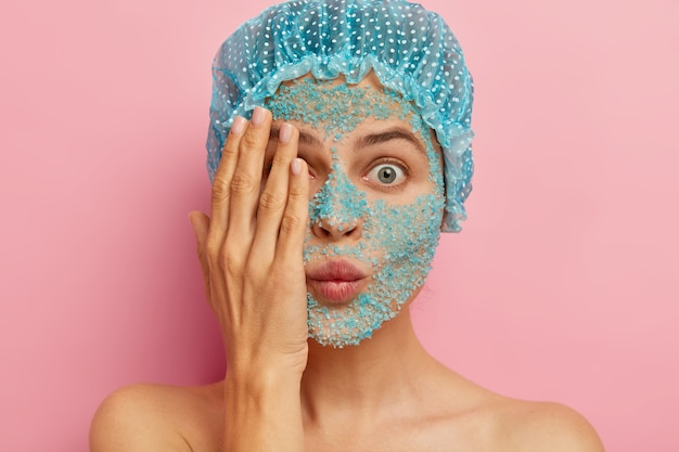 Close-up shot van verbaasde vrouw met blauwe scrub op gezicht, bedekt één oog met hand, probeert zichzelf te verbergen, heeft een verbijsterde uitdrukking, draagt een beschermende badmuts, wil er jonger uitzien, staat shirtless