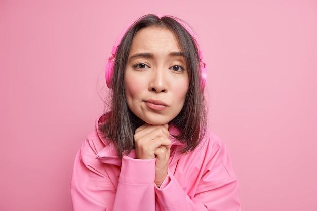 Close-up shot van verdrietig teleurgesteld millennial meisje houdt handen onder kin kijkt met melancholische uitdrukking luistert songteksten liedjes via koptelefoon gekleed in jas geïsoleerd over roze muur