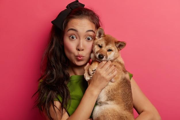 Close-up shot van verrast donkerharige etnische vrouw houdt shiba inu-hond in de buurt van gezicht, houdt lippen rond, voelt verbondenheid met loyaal dier