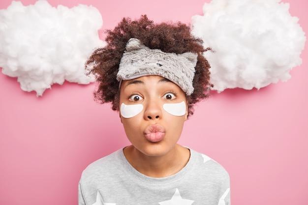 Close-up shot van verrast vrouw houdt lippen gevouwen en stuurt mwah op camera ondergaat schoonheidsbehandelingen voordat ze gaat slapen gekleed in nachtkleding zachte blinddoek op voorhoofd