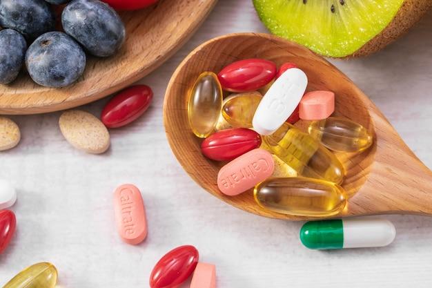 Close-up shot van vers fruit met verschillende medicijnen op een houten lepel