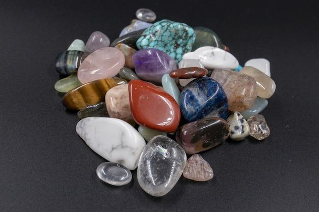 Close-up shot van verschillende gepolijste natuurlijke minerale stenen tegen een zwarte achtergrond