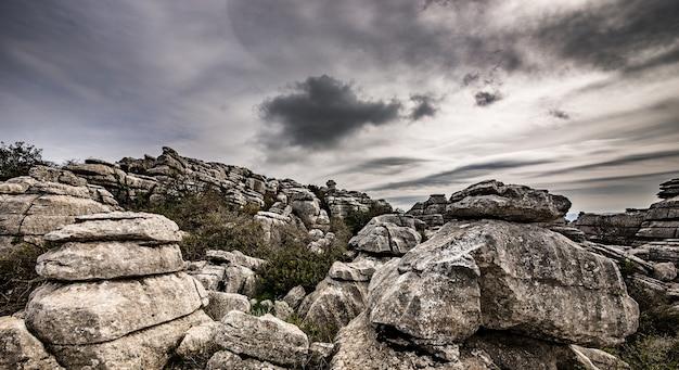 Close-up shot van verschillende grijze rotsen boven op elkaar onder een bewolkte hemel