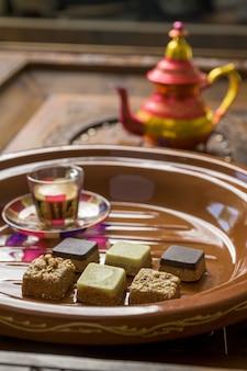 Close-up shot van verschillende soorten vierkante snoepjes met thee op een houten dienblad