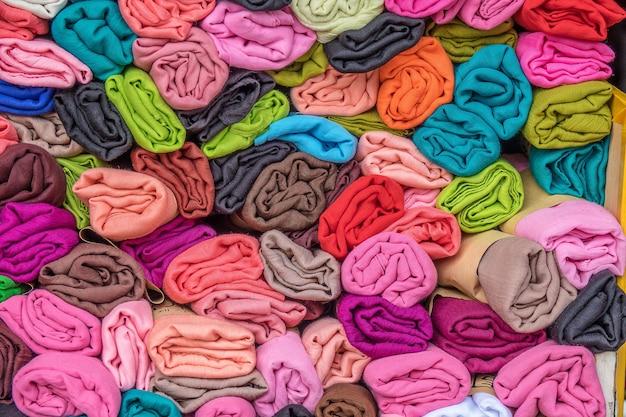 Close-up shot van verschillende stukken veelkleurige kleding op elkaar gestapeld