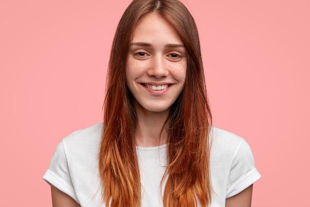 Close-up shot van vriendelijk ogende vrouw met positieve uitdrukking, charmante glimlach heeft, staat tegen roze achtergrond. mensen en emoties concept