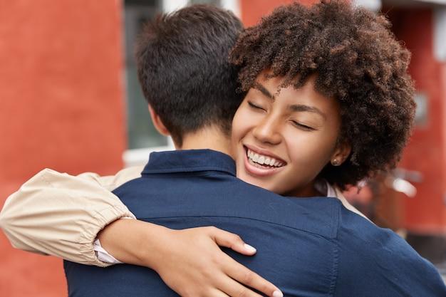Close-up shot van vrolijke afro meisje geeft warme knuffel aan haar broer
