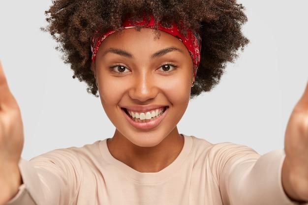 Close-up shot van vrolijke donkere meisje praat met vriendje via online video, maakt selfie met onherkenbaar apparaat, heeft een brede glimlach, modellen over witte muur, trekt handen naar voren
