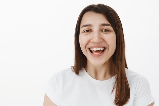 Close-up shot van vrolijke gelukkige europese brunette met perfecte witte glimlach oprecht hardop lachen en vreugdevol staren, opgetogen met plezier tijdens hilarische gebeurtenis over grijze muur